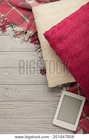 Knitted pillows plaid and eBook on a light wooden background. Top view. Flat lay.