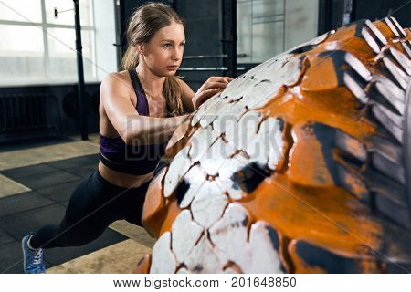 Portrait of strong young woman flipping heavy tire during weights workout in modern gym