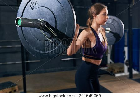 Portrait of beautiful strong woman lifting heavy barbell performing shoulder press during workout in modern gym