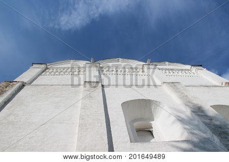 Courtyard of Spaso-Prilutsky Monastery in the Vologda city, Russia. Summer sunny day. White church. Part of the building. Unusual angle of view from the bottom up