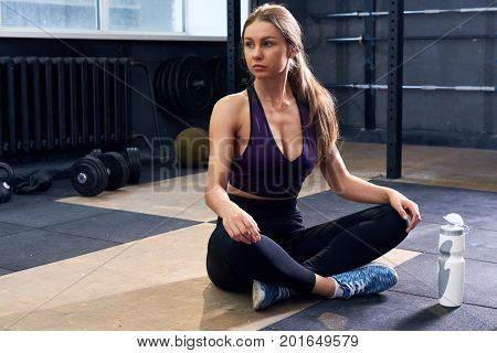 Portrait of young woman sitting cross legged on floor preparing for fitness  workout in modern gym