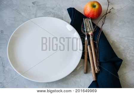 White Round Plate, Red Apple And  Tree Brunches On A Wooden Background. Autumn Holidays Concept.