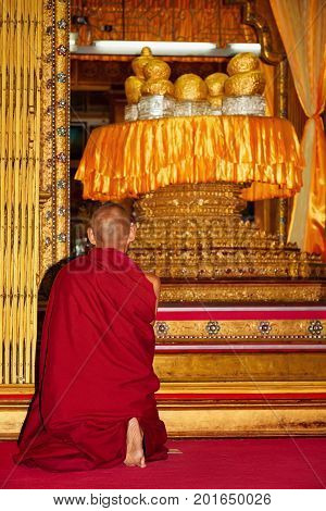 Monk praying in front of shrine with sacred Buddha figures covered by gold leaves in buddhist temple Hpang Daw U on Inle lake in Myanmar. Traditional arts culture and religion of Burmese people.