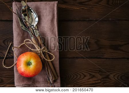 Tree branches, apple, cutlery on a linen sackcloth on a wooden background. Copy space and top view. Autumn mood, Halloween, Thanksgiving, Holiday concept.