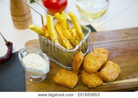 Chicken Nuggets And Chips With Sause On Wooden Cutting Board