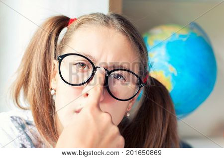 Smart thoughtful nerdy teenage girl wearing black eyeglasses and thinking seriously. Vibrant indoors horizontal image.