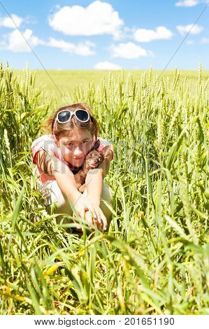 Young teenage girl sitting in wheat field holding her lovely little toy-terrier dog. Multicolored vibrant outdoors summertime vertical image with cloudy sky background.