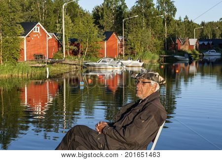 KOKKOLA, FINLAND ON JULY 07. View of an old gentleman relax this side boathouses along the channel on July 07, 2017 in Kokkola, Finland. Evening and sunshine. Editorial use.