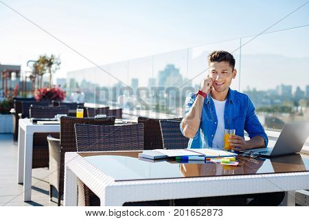 Hello dude. Cheerful young gentlemen in casual enjoying his fresh orange juice while sitting at a laptop and having a pleasant conversation with a college friend.