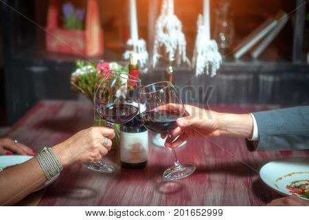 romantic couple with glasses of red wine on a date in a cozy Italian restaurant. Leisure, drinks, people and holidays concept - happy man and woman clinking glasses.