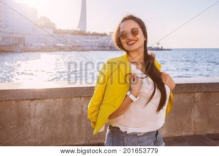 Young stylish woman wearing bright colorful blazer and sunglasses walking on the city street. Casual fashion, fall look. Plus size model.
