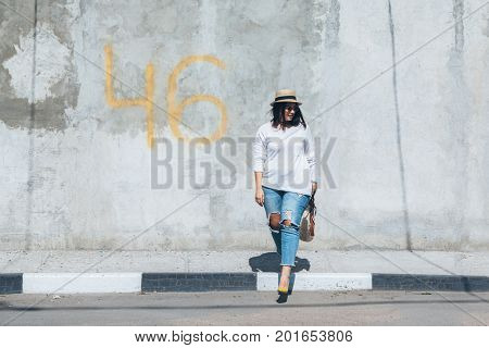 Young fashion woman wearing ripped jeans, colorful heels and straw accessories posing over gray concrete city wall. Plus size model.