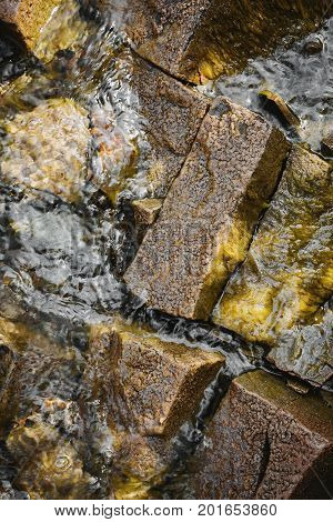 Stones in water. One beautiful wet polished stone above water surface.