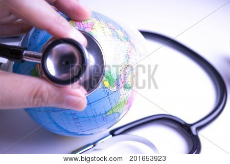 close up hand with stethoscope auscultating world