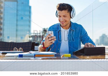Inspired and ready to work. Low angle view on a relaxed young man wearing headphones enjoying the music playing while sitting on a terrace of a cafe and preparing his home assignment for tomorrow.
