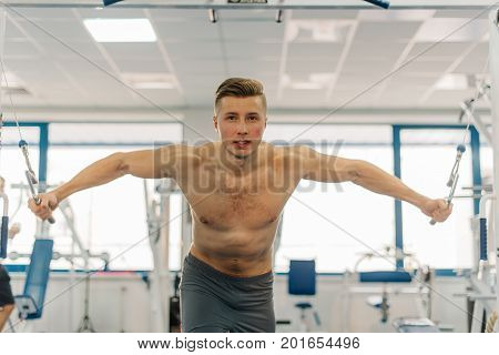 Strongman working out on Fitness-station. Man with six-pack abs. He working out to become jacked, develop strength.