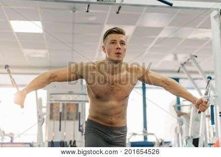 close up photo of beautiful man training on Fitness-station. Guy has strong hands. He working out to develop strength, develop definition of muscles