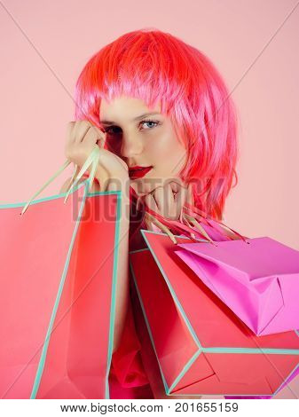 Holidays celebration concept. Fashion shopper posing on pink background. Woman with shopping bags. Sale and black friday. Girl wearing red wig.