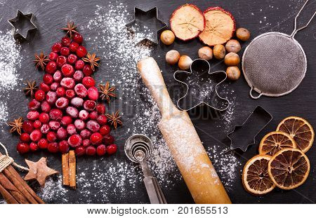 Christmas food. Ingredients for cooking Christmas baking: fir tree made from frozen cranberries kitchen utensils and dried fruits on a dark table top view