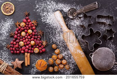 Christmas food. Ingredients for cooking Christmas baking: fir tree made from dried cranberries with nuts kitchen utensils and dried fruits on a dark table top view