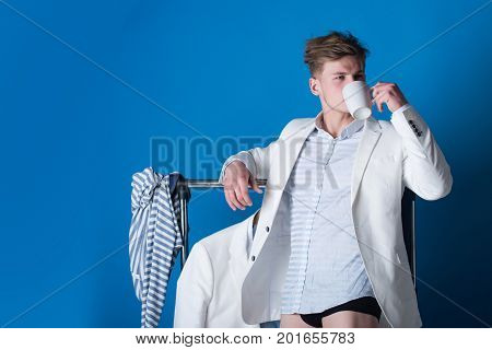 Man drinking from cup. Macho wearing shirt jacket and underpants. Model with muscular legs in dressing room. Clothes rack on blue background. Fashion and underwear concept.