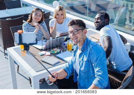 Say cheese. Top view on four young friends of different cultures sitting in a cafe and looking at a smartphone fixed on a selfie stick while taking a self portrait on a terrace.