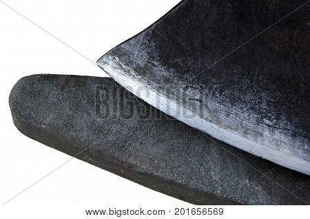 Old sharpening stone and a blade of an ax as the concept of tool sharpening isolated on a white background