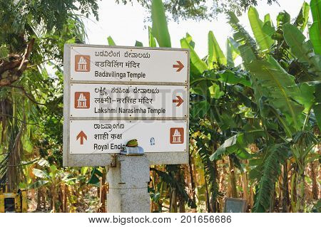 Hampi, India - November 20, 2012: Signpost for tourists with the pointer to the ancient ruins of Hampi - Badavilinga Temple Lakshmi Narasimha Temple in Hampi, Karnataka, India.