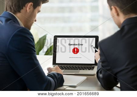Two businesspeople looking at broken laptop screen with sudden system failure message, windows not working, hanging computer, critical fatal operation error with all data lost, close up rear view