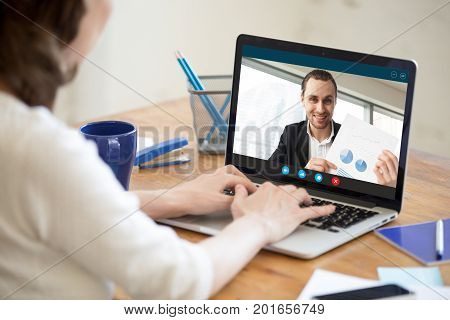 Businesswoman talking on video conference to businessman showing document at webcam, colleagues discussing work by video call application, financial consultant consulting client online, close up view