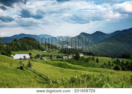 Carpathian mountains summer landscape with cloudy sky and village, natural summer travel background