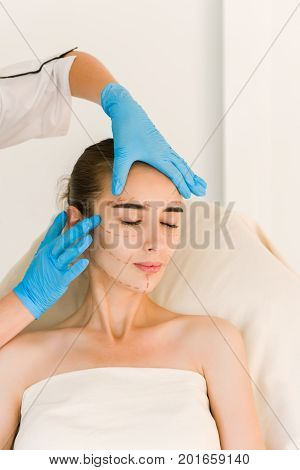 Cosmetic surgeon examining female client in office. Doctor checking woman's skin before plastic surgery. Surgeon or beautician hands touching woman face.
