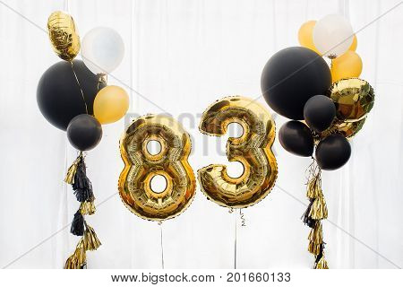 Decoration for birthday, anniversary, celebration of the eighty three anniversary, white background, gold and black balloons with tassels