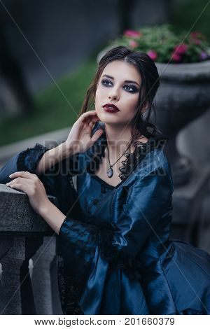 Woman dressed in blue victorian dress stand near old building