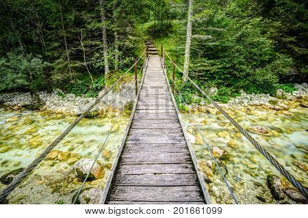 Old wooden plank bridge across beautiful river. Overcoming an obstacle concept. Soca River, Triglav National Park, Slovenia.