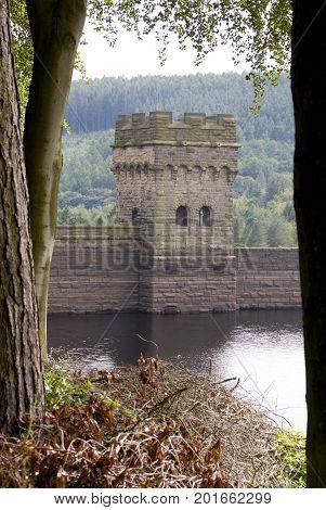 DERBYSHIRE UK - 24 Aug: Lower Derwent Reservoir tower frames between tree trunks on 24 Aug 2014 in the Peak District, Derbyshire, UK