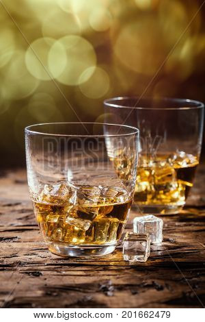 Whiskey with ice in glasses on rustic wood background, copy space