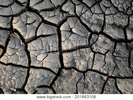Dry land. Dry earth. Dry soil. Grey soil. Gray soil. Soil texture. Soil background.  Earth background. Earth texture. Nature background.Cracked earth. Grunge. Grunge background. Earth pattern. Drought. Natural background.