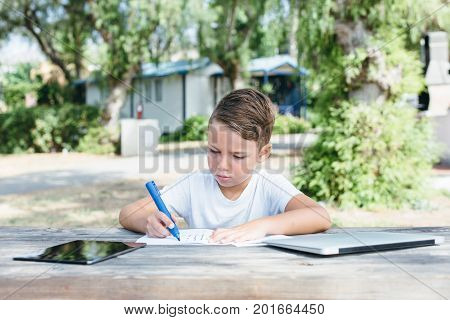 Little serious kid drawing in notebook while sitting at wooden table with gadgets and studying in garden.