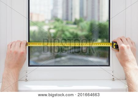 The employee makes a measurement of the glass in a plastic window using a tape measure.