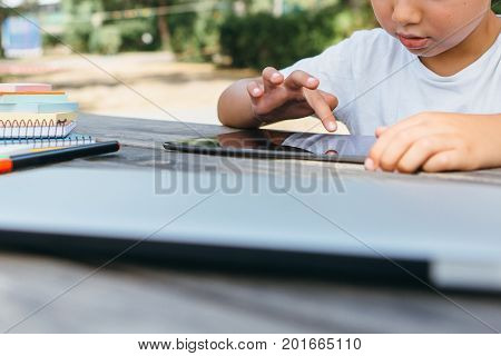 Crop shot of schoolboy posing at table with notebooks and browsing tablet on background of summer yard.