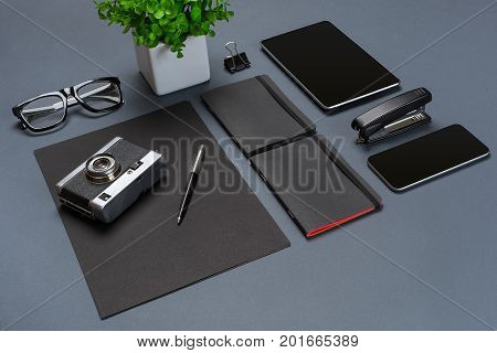 A set of black office accessories, glasses, old camera and tablet on gray background. Flat lay. Still life. Mock-up