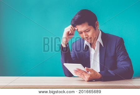 Businessman sitting at wood table and green wall and looking down at tablet computer screen at officeFeeling stress about financial crisisstock market failure.