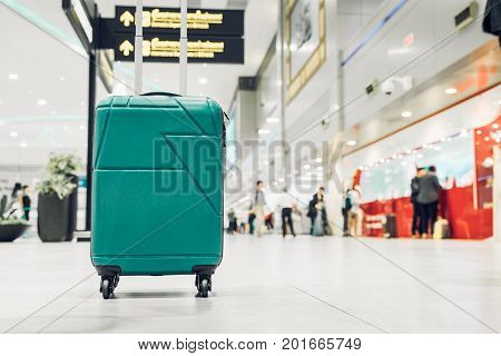 Suitcases in airport departure terminal with traveler people walking in backgroundHoliday vacation concept Business tripselective focus on suitcases.