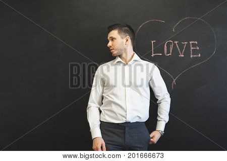 Man standing over word Love on chalkboard and looking away. Boyfriend waiting love