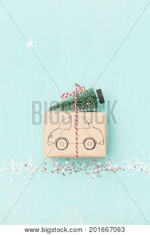 Top view on Christmas gift wrapped in craft gift paper decorated with car drawing with Christmas tree on turquoise wooden background with sparkling stars. New Year holidays and celebration concept