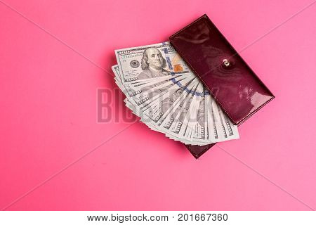 A lot of dollar bills in a red woman's purse on pink background. Top view. Copy space. Still life