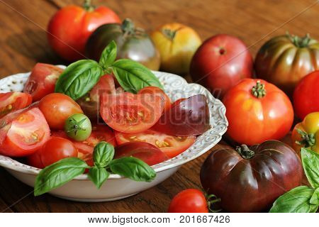 Colorful tomatoes salad with basil and balsamic vinegar on wooden rustic background .