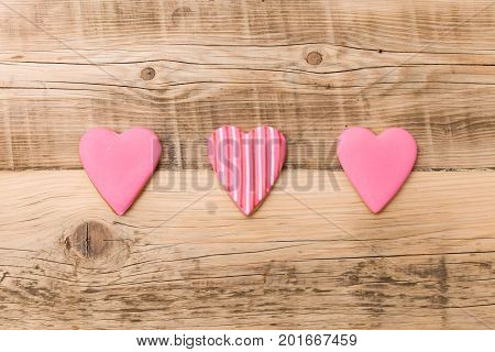 Top view on three little gingerbread cookies in shape of hearts on retro wooden background. Flay layout. Love Valentines's day concept