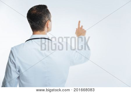Contemporary medicine. Waist up shot of a mature medical worker looking at an invisible wall while touching and using an invisible touchscreen.
